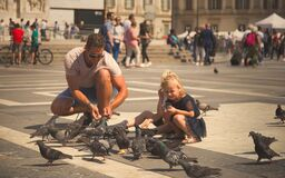Father and daughter in a shared moment they play with the pigeons in Piazza Duomo in Milan