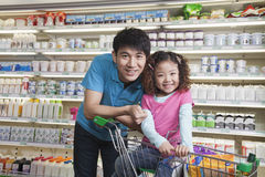 Father and Daughter Shopping in Supermarket, Looking at camera Stock Photo