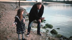 Father and daughter on the shore, little girl throw stone into the water. Man show to girl how play stone skipping. stock video footage