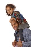 Father and daughter shoulder ride smiling. Afro father giving little daughter a shoulder ride, both smiling Royalty Free Stock Images