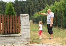 Father and daughter. Father showing something his daughter - little girl - behind fence Stock Photography