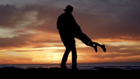 Father and daughter silhouettes playing on beach at sunset. Summertime vacations