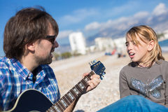 Father and daughter singing song on beach Stock Photography