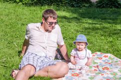 Father and daughter sit on the grass in the park Stock Images