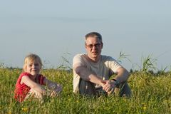 Father with daughter sit on meadow Royalty Free Stock Photography