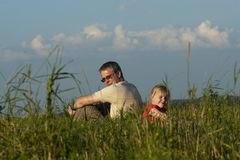 Father with daughter sit on meadow Stock Photography