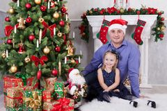 Father and daughter sit near the Christmas tree. Father have a Santa Claus hat on his head. A fireplace behind them.  royalty free stock images