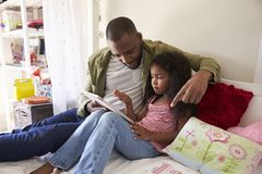 Father And Daughter Siting On Bed Using Digital Tablet Stock Photos