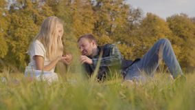 Father and daughter sitting on the autumn meadow and chatting. Caucasian man and young blonde girl dressed in casual. Clothes spending time together outdoors stock footage