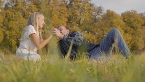 Father and daughter sitting on the autumn meadow and fighting for the apple. Caucasian man and young blonde girl dressed. In casual clothes having fun together stock video footage