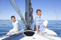 Father and daughter (8-10) sitting back to back at bow of sailing boat, smiling, side view, portrait Stock Image