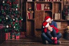 Father and daughter are sitting on the floor embracing and waiting for Christmas. stock photos