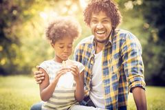 Father and daughter sitting on grass. stock photography