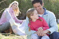Father and daughter sitting in grass, mother in background Stock Photography