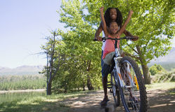 Father and daughter (7-9) sitting on mountain bike on lakeside woodland trail, girl with arms raised, low angle view Royalty Free Stock Photo