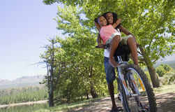 Father and daughter (7-9) sitting on mountain bike on lakeside woodland trail, girl on handlebars, low angle view (tilt) Royalty Free Stock Photos