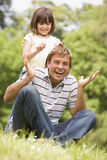 Father and daughter sitting outdoors with flowers stock photos