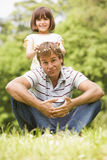 Father and daughter sitting outdoors with flowers Stock Images