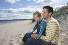 Father And Daughter Sitting On Sandy Beach Stock Photos