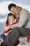 Father and daughter (7-9) sitting on sled in snow field, smiling, portrait Stock Image