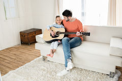 Father and daughter sitting on sofa and playing guitar together Stock Image