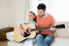 Father and daughter sitting on sofa and playing guitar together Stock Photos