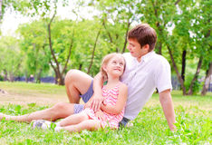 Father and daughter sitting together on the grass Stock Photo