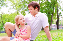 Father and daughter sitting together on the grass Stock Photos