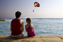 Father and daughter sitting together on piers Royalty Free Stock Images