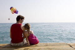 Father and daughter sitting together on piers Stock Image