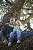 Father and daughter (3-5) sitting in tree, portrait, low angle view Royalty Free Stock Photo