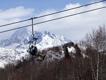 Father and daughter on ski-lift at winter sun day Stock Image