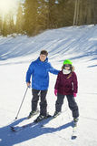 Father and daughter skiing together Stock Photo