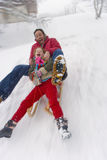 Father and daughter sledding down snow slope Stock Photo