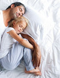 Father and daughter sleeping on bed royalty free stock photography
