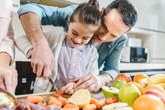 father with daughter slicing vegetables and fruits stock image