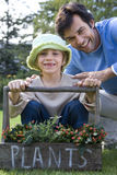 Father and daughter (5-7) smiling, girl holding handle of plant box, portrait Royalty Free Stock Images