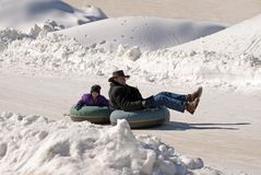 Father and daughter/snow tubes. A man and his daughter riding down a slope on their snow tubes royalty free stock images