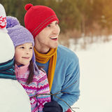 Father and daughter with snowman Stock Photo