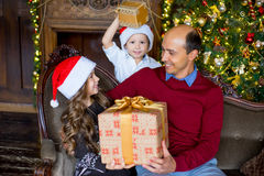 Father, daughter and son with Christmas gifts sitting on the sof Royalty Free Stock Images