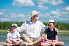 Father with daughter and son sits on a beautiful pier on the lake royalty free stock image