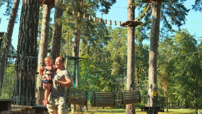 Father and daughter spend leisure time together in rope park stock video