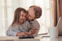 Father and daughter spending time together. Man pampering his little daughter sitting with laptop computer and coffee cup on the table. Father spending time with stock photography