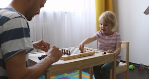 Father and daughter spending time together and playing chess stock footage