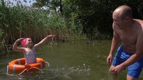 Father and daughter splash water. Girl with swimsuit and headscarf in lifebuoy. Happy father and daughter splash each other with lake water. Cute girl with stock video footage