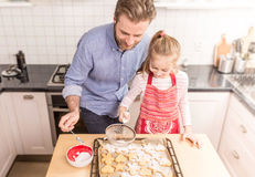 Father and daughter sprinkling powdered sugar on cookies Royalty Free Stock Photos