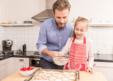 Father and daughter sprinkling powdered sugar on cookies Royalty Free Stock Photo