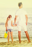 Father with daughter standing back forward on sandy beach on vac Stock Photos