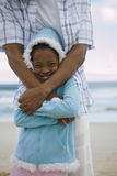 Father and daughter (7-9) standing on beach, girl wearing blue fleece with hood, smiling, portrait royalty free stock photography