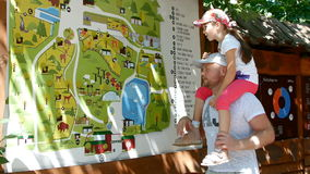 Father and daughter are studying the map of the zoo stock video